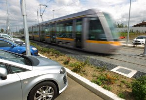 Luas passing parked cars at speed.