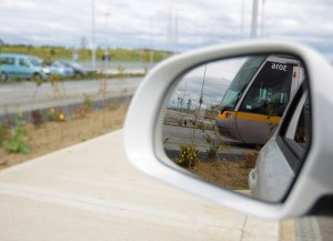 Luas tram reflected in car wing mirror.